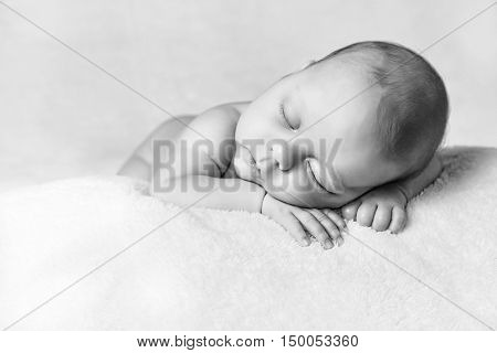 Portrait of sleeping newborn baby, holding his hand close to his face like he is listening to the music. Cute little child resting on the blanket.