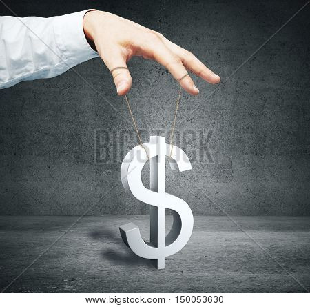 Male hand controlling dollar sign as puppet on concrete background. Price manipulation concept