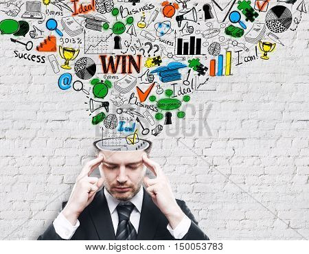 Pondering young businessman with business sketch coming out of his head on brick background. Brainstorming concept