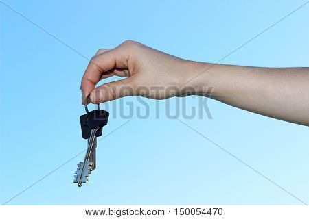 hand holding keys over light blue background