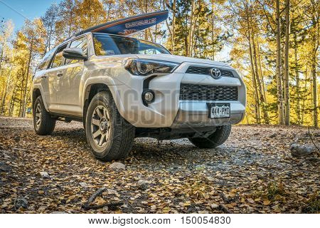 BASALT, CO, USA - SEPTEMBER 27, 2016: Toyota 4Runner SUV (2016 Trail edition) carrying  a paddleboard on Frying Pan Road with fall colors in Colorado's Rocky Mountains