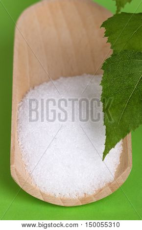 Xylitol birch sugar on wooden scoop with birch leaves over green. White granulated sugar alcohol, substitute used as sweetener that taste like table sugar, extracted from the wood of birch trees.