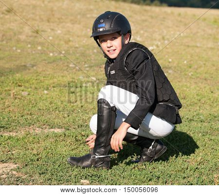Young girl in helmet and protection vest before showjumping competition