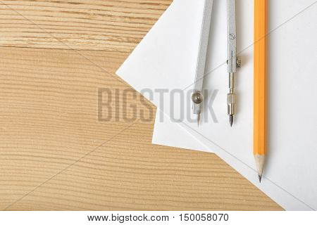 Layout with pencil and compass on white paper which is on wooden surface. Top view composition. Engineering stuff. Work place of draftsman, architect, constructor. Construction and architecture. Measurement.