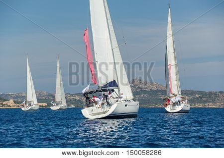Group of sailboats under the hoisted sails near the Sardinia shores, view from the stern. Sardinia, Italy.