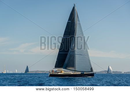Luxury big sailing yacht with black sails horizontal photo. Sardinia, Italy.