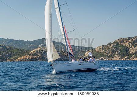 Cruising sailboat near Sardinia island shores. Mediterranean sea cruising, Italy.