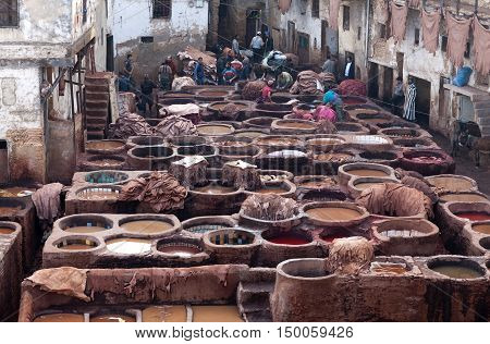 FEZ, MOROCCO - JANUARY 4, 2014: Men working hard in the tannery souk in Fez, Morocco