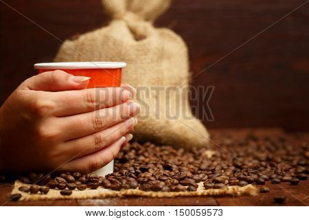 Female hands holding a cup of coffee with beautiful foam on the background of brown wooden table with burlap sack and scattered coffee beans. Focus on hands and cup. Shallow dof.