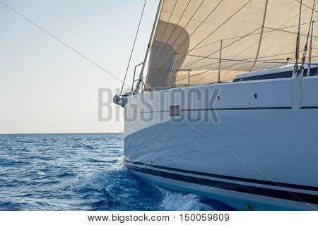 Sailing yacht bow with hoisted headsail, view from she's tender. Mediterranean sea, Sardinia, Italy.
