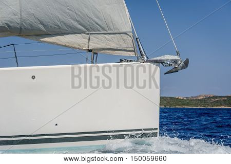Sailboat bow with hoisted headsail and copy space on the boat hull. Mediterranean sea, Sardinia, Italy.