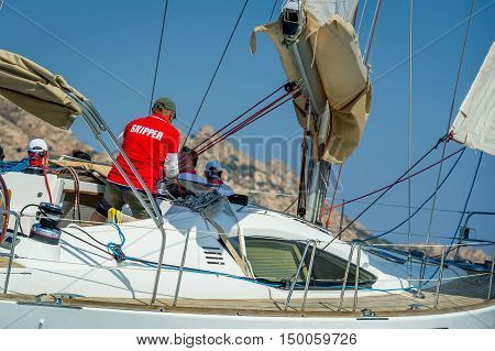 Skipper in red t-short is working with a winch of his sailing boat. Sailing regatta in the Mediterranean sea.