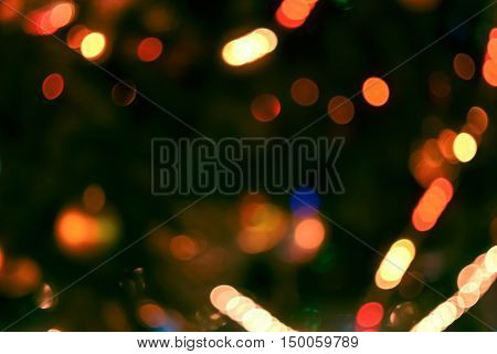 Christmas lights background. Blurred electric garland on Christmas tree. Red green yellow orange blue glow