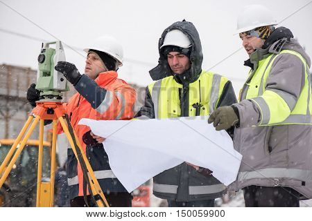 Civil Engineers at construction site are inspecting ongoing production according to design drawings.