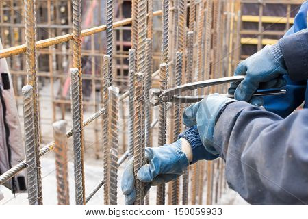 Worker at construction site is preparing reinforcement cage.