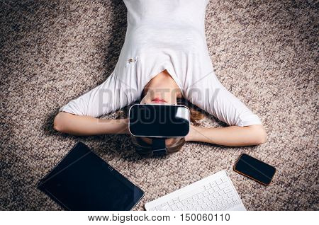 Woman with virtual reality goggles lie on a carpet between mobile and notebook. Studio. Woman show a gesture.