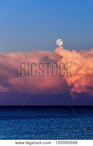 Full moon emerging from behind some clouds on the Mediterranean sea in Torrevieja, Alicante Spain