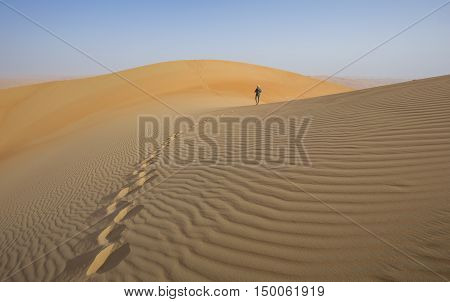 A person in Liwa desert that covers large area in Oman, UAE, KSA and Yemen