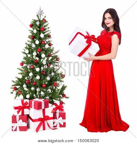 young beautiful woman in red dress with big gift box and decorated christmas tree isolated on white background