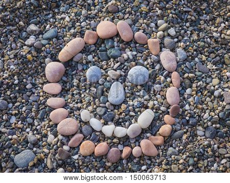 Stone smile face with pebbles on beach