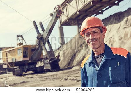 worker in front of heavy excavator loading gravel into train