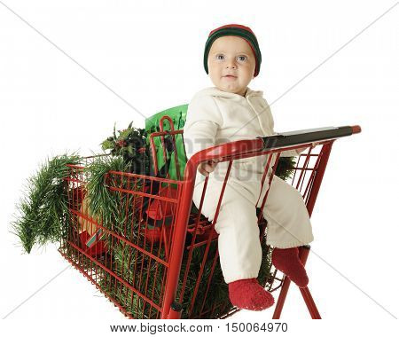 An adorable baby boy happily riding in the child's seat of a red shopping cart filled with Christmas goodies.  On a white background.