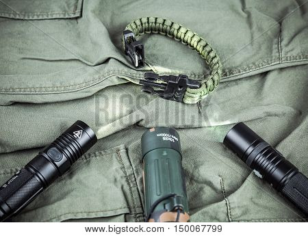 Military paracord bracelet, tactical torch and spy-glass on army-green fabric