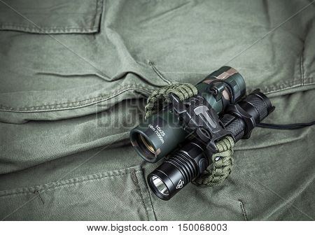 Military paracord bracelet, tactical torch and spy-glass on army-green fabric poster
