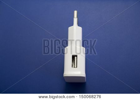 AC power supply adapter on blue leather background.