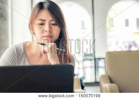 Pretty young asian woman holding a pen and thinking while sitting in coffee shop with her laptop.