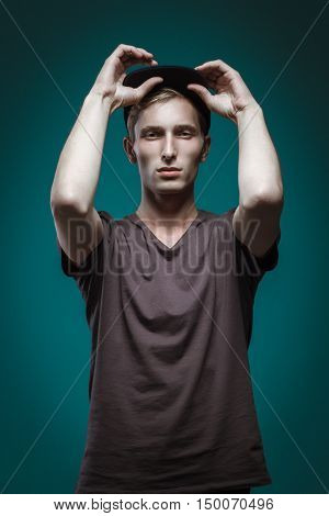 Handsome Man In Black T-shirt And Cap Posing On Blue Background. Model Tests