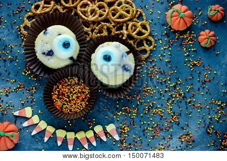 Halloween background sweet treat for kids candy corn one eye cupcakes sugar sprinkling cookies shaped funny monster face top view with copy space