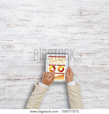 Top view of businesswoman hands using tablet pc with diagrams and graphs on screen