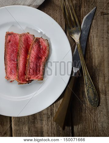 Rare steak medium roast with spices on a plate, knife and fork on a wooden background