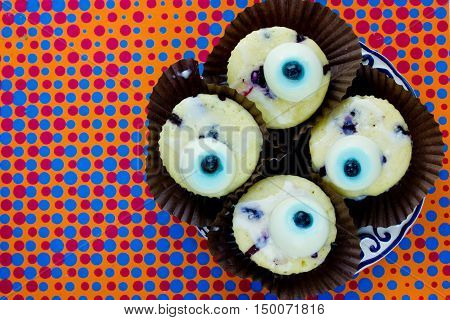 Monster eye cupcakes for Halloween party on colorful background top view blank space for text