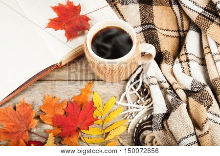 Hot drink in a large cup, book, colorful autumn leaves on a wooden table surface