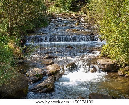 Fast flowing stream in the Carpathian Mountains overcoming rapids and ledges of rock