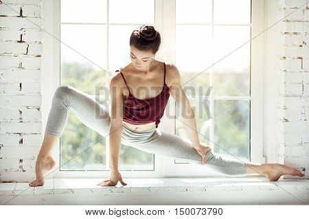 Showing professionalism. Talented young hard working dancer standing on the windowsill and looking down while concentrating on her movements
