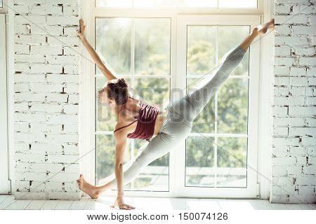 Impressed with professionalism. Skillful attractive experienced dancer doing the splits in the air and touching the wall while having a dance class