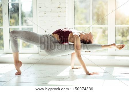 Hard work and persistence. Beautiful gifted professional dancer bending and holding her leg while performing a difficult exercise