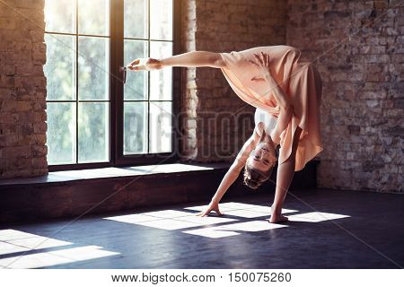 High professionalism. Masterful gifted attractive dancer standing upside down and holding her leg up while having a workout
