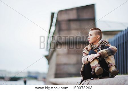 a beautiful short-haired girl sitting on the parapet with his legs in boots