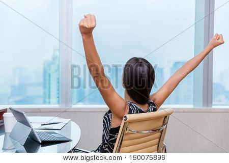 Winning office worker working woman with arms raised up outstretched in success of career goal achievement. Happy successful businesswoman looking at city view in work window.