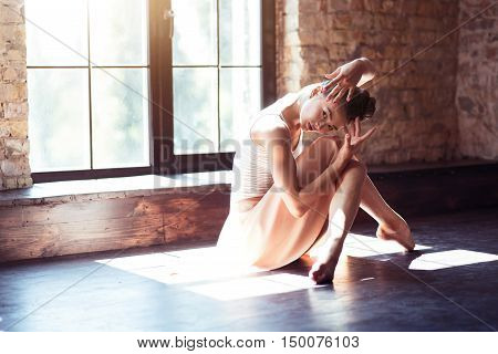 Enigmatic look. Gorgeous elegant brunette woman moving her hands and looking to the right while sitting next to the window