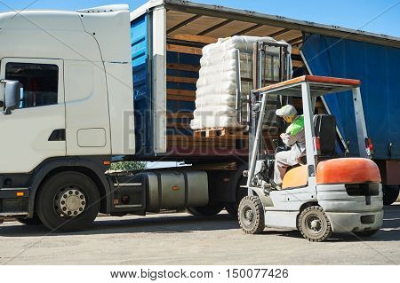 Loading works. Forklift with load and lorry truck