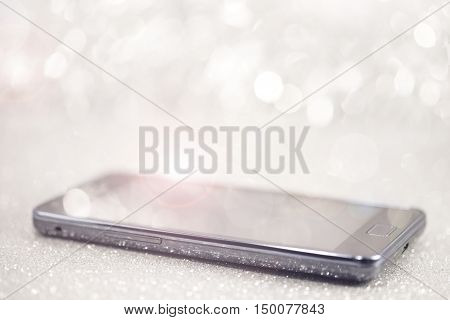 Mobile phone on shiny sparkle silver background