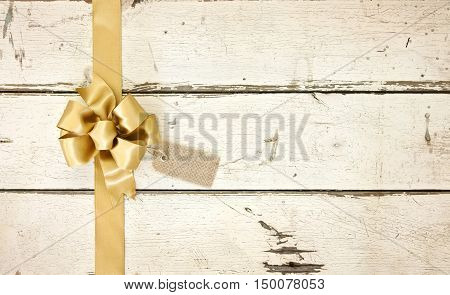 A gold Christmas bow and ribbon with a tag on a rosy white distressed wood background