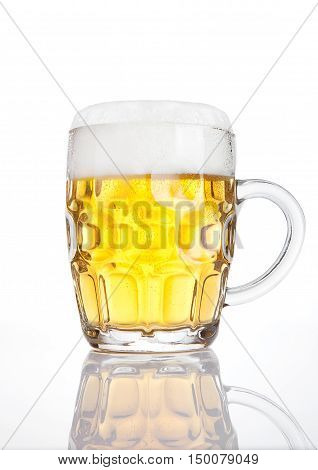 Vintage glass of beer with foam with reflection on white background