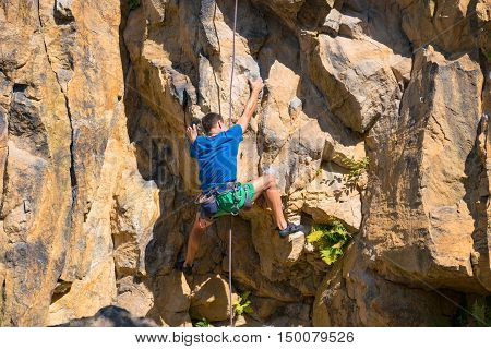 Male rock climber climbing up a cliff