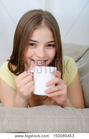Portrait of young brunette woman sitting on couch in her living room and drinking coffee or tea.